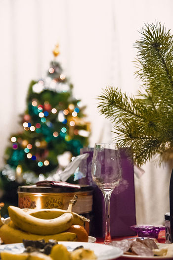 Close-Up Of Wine Glass With Food On Table Against Decorated Christmas Tree