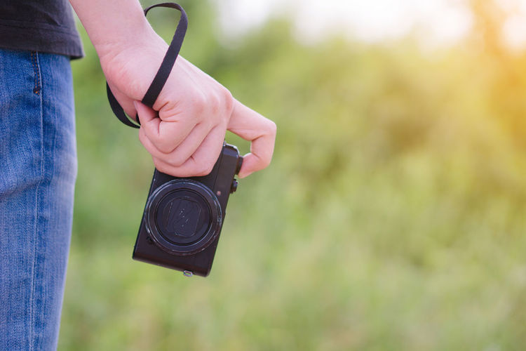 Midsection of woman photographing outdoors