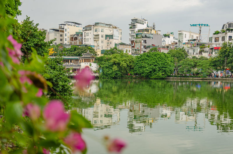 Scenic view of lake by buildings in city