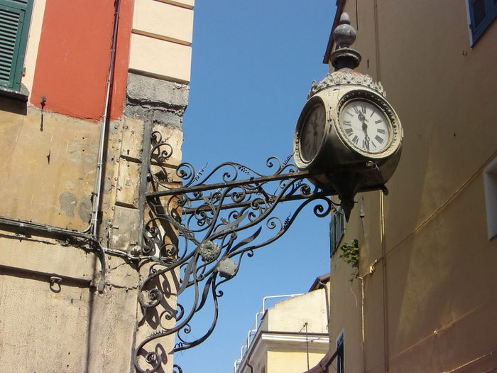 Low angle view of antique clock amidst buildings