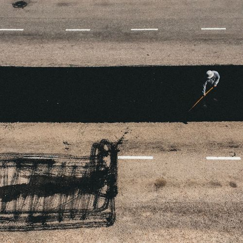 High angle view of worker sweeping road