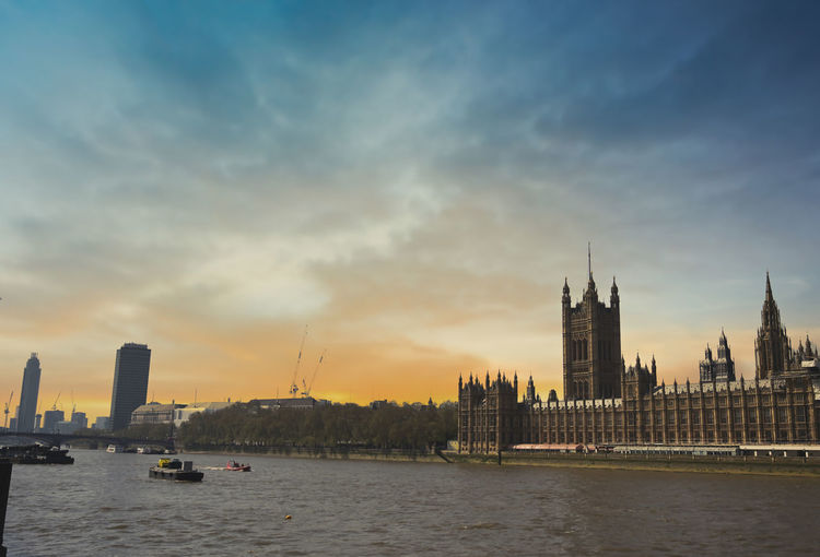 View of river and buildings against sky during sunset
