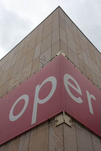 """Text: """"Oper"""" on a red banner at the corner of a house Architecture Built Structure Close-up Corner Corner Of The Building Day Horizontal House Low Angle View No People Oper Opera House Outdoors Red Text Banner Sky Text Text Oper"""
