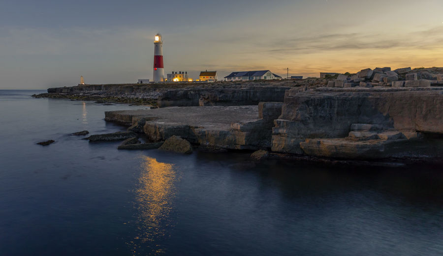 Illuminated lighthouse by sea against sky during sunset