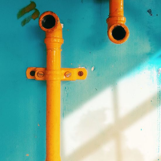Close-up of yellow pipe on wall
