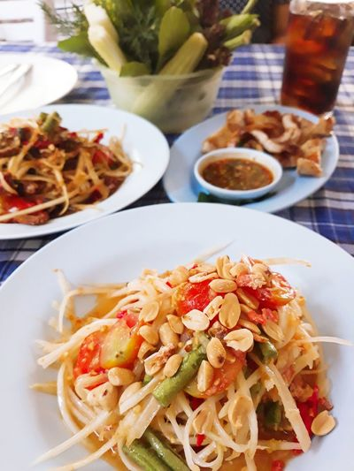 Close up spicy papaya salad with northeast style cuisine on the table. mealtime อาหารไทย อาหารอีสาน Vegetables Local Food Tasty Eating Northeast Fried Bean Tomatoes String Beans Lime Juice Sour Chili  Spicy Food Food Spicy Papaya Salad Grilled Pork Dishes Ingredients Plate High Angle View Close-up Food And Drink Prepared Food