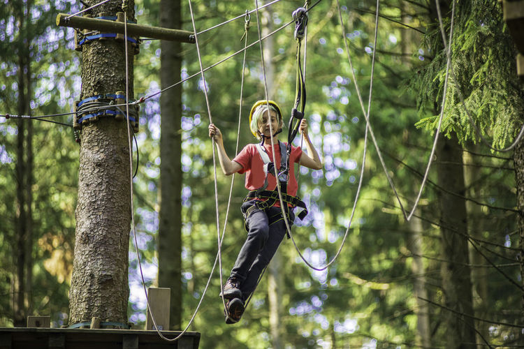 Boy hanging on rope in forest