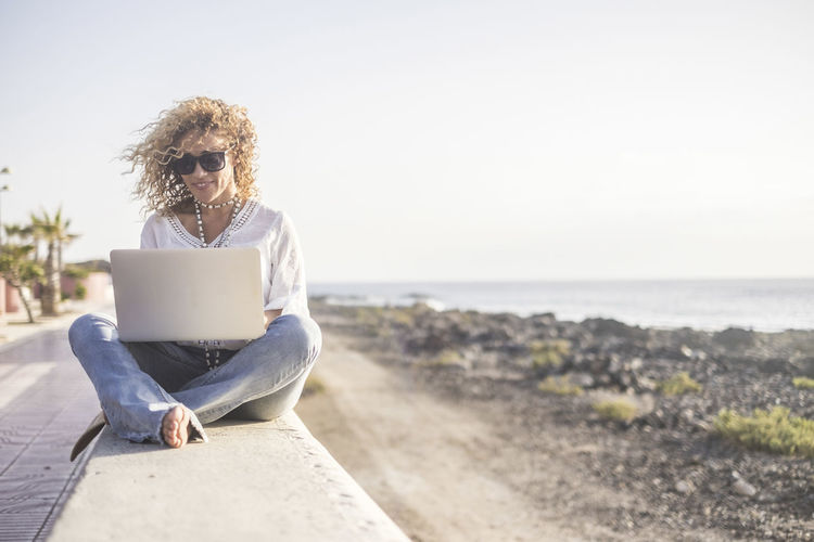 Technology and travel. Working outdoors. Freelance concept. Pretty young woman using laptop beach. Sitting Sea One Person Leisure Activity Water Laptop Casual Clothing Computer Technology Using Laptop Wireless Technology Real People Nature Sky Lifestyles Land Young Adult Relaxation Horizon Over Water Outdoors Adult One Woman Only Sitting Curly Hair Working Coastline Relaxing Pretty Females Caucasian Freelance Life Smiling Beautiful People Nomadic Freelance Blogging Window Beachphotography Nature_collection