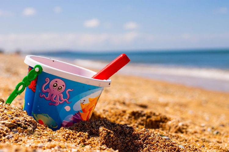 Close-up of paper toy on sand at beach against sky