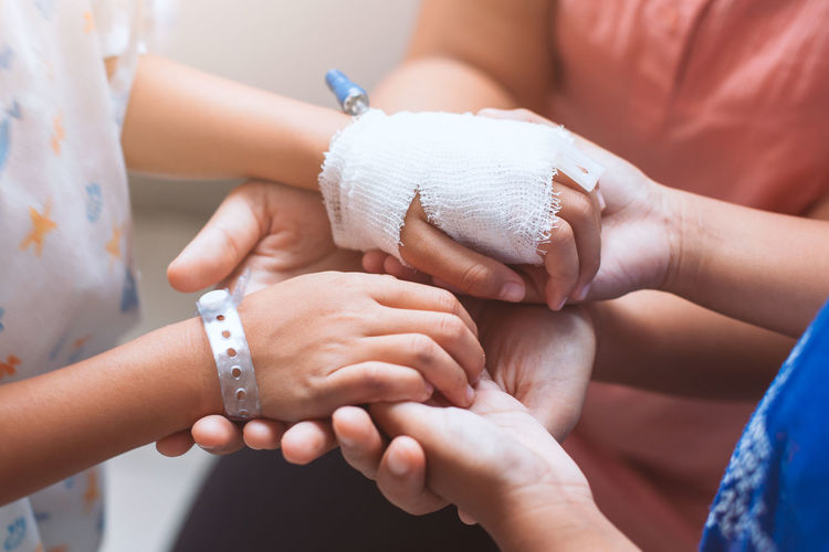 Mother and daughter holding hand who have IV solution bandaged together with love and care in the hospital Aid Asian  Care Family Hospital Kids Love Sister Bandage Care Child Flu Friend Girls Hand Healthy Holding Human Body Part Human Hand Medical Sibling Sick Sickness Treatment Women