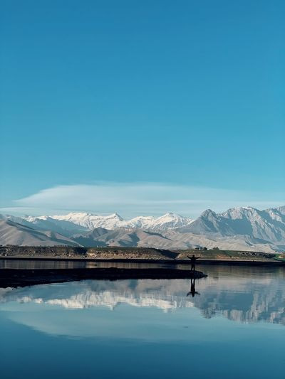 Scenic view of lake and snowcapped mountains against blue sky
