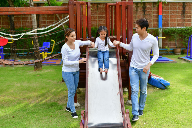Girl Holding Hands Of Father And Mother While Sliding On Slide At Park