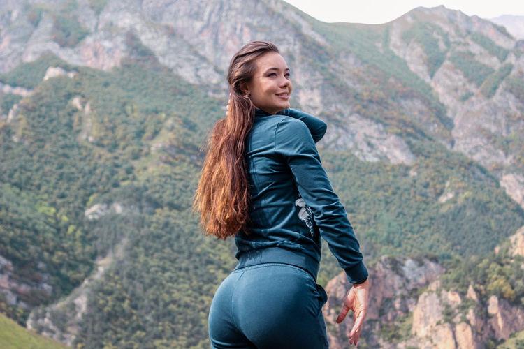 Beautiful woman standing against mountain range
