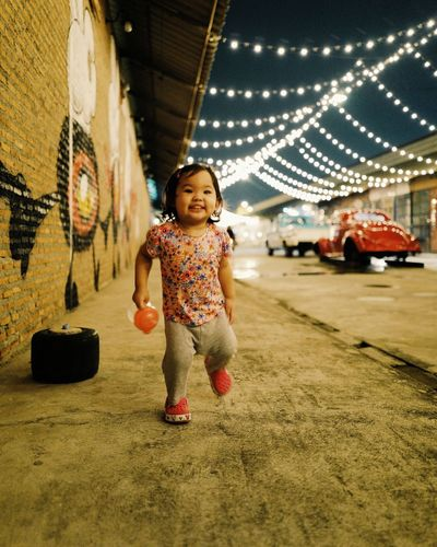 Full length portrait of cute baby girl walking on footpath at night
