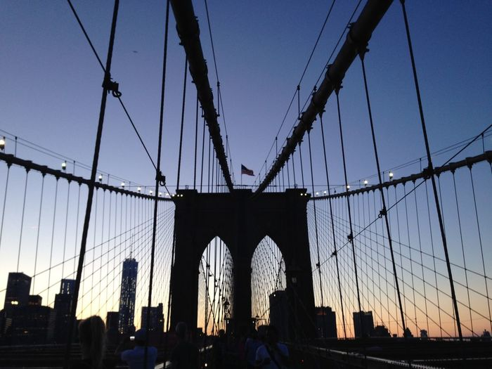 People On Brooklyn Bridge In City During Sunset