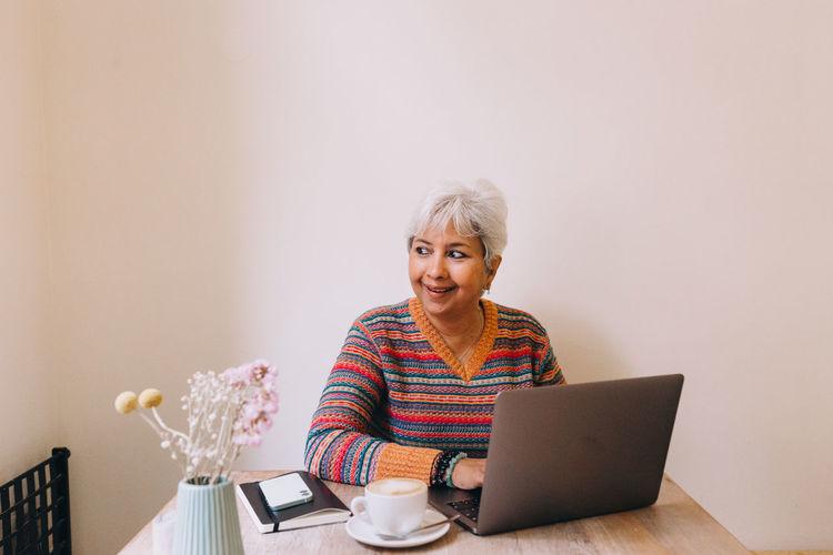 Portrait of smiling woman using laptop