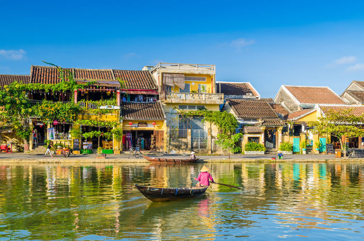 Woman crossing a river on a boat in Hoi An during mid day Architecture Boat Bright City Colorful Culture Day Heritage Hoi An House Old Reflection Sky Sunny Tourist Transportation UNESCO World Heritage Site Vietnam Vintage Water Yellow