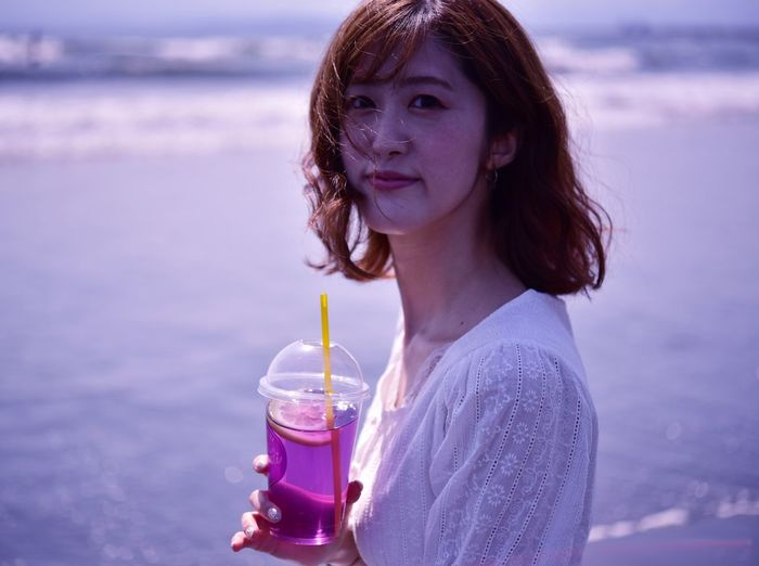 Portrait of woman drinking juice standing on beach