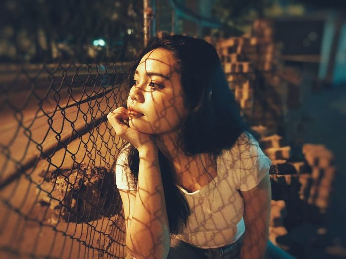 Thoughtful woman looking through chainlink fence while sitting outdoors at night