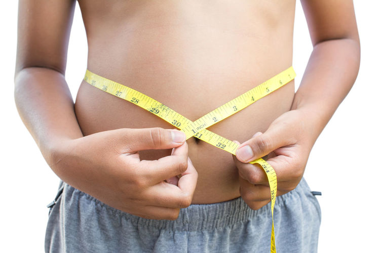 Midsection Of Shirtless Boy Measuring Waist Against White Background