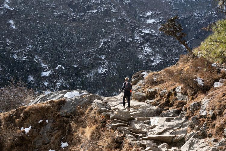 People walking on rocks against mountains