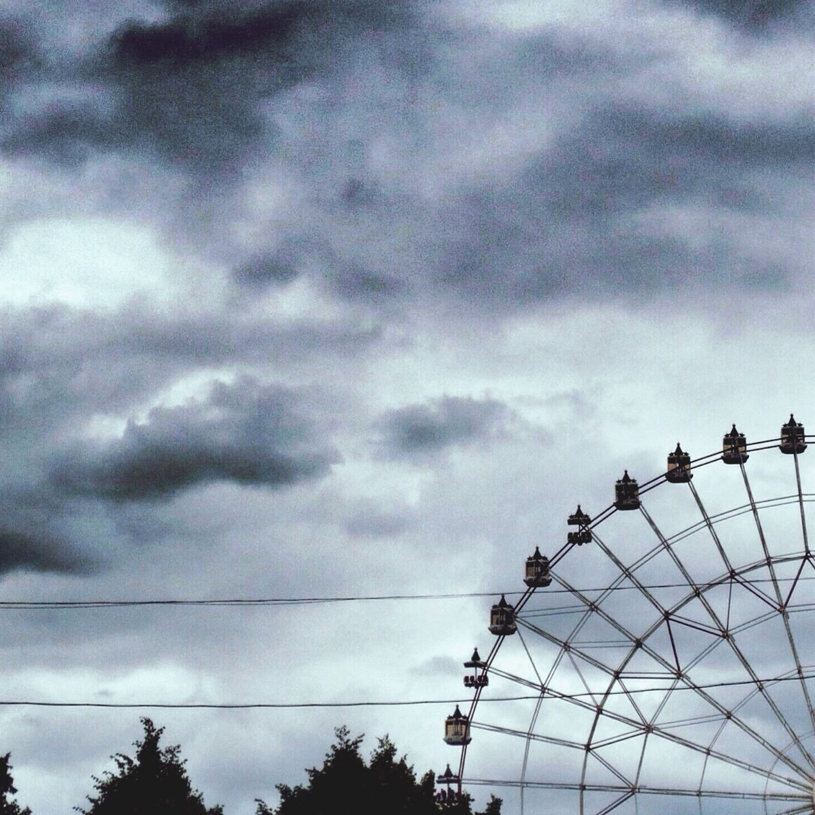 low angle view, sky, cloud - sky, cloudy, built structure, ferris wheel, architecture, cloud, amusement park, arts culture and entertainment, amusement park ride, silhouette, overcast, day, outdoors, tall - high, no people, building exterior, weather, metal
