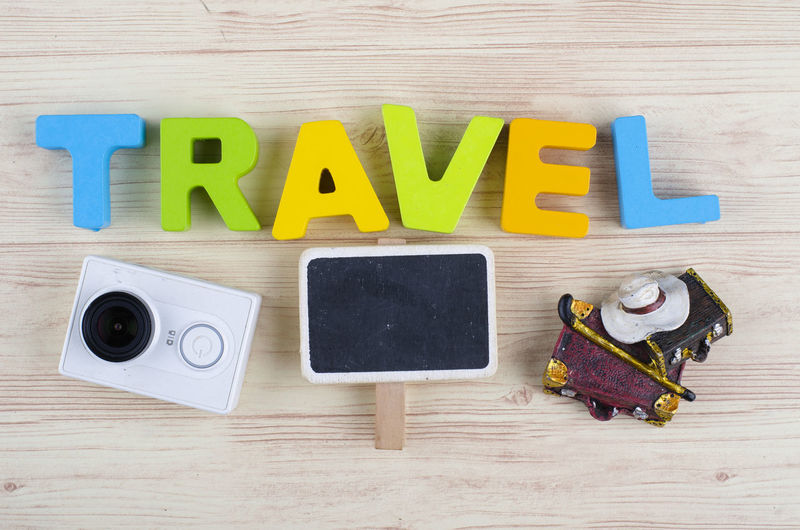 top view vacation and holiday concept word TRAVEL with accessories on wooden background Wood - Material Table Indoors  Still Life Text Directly Above Communication High Angle View Capital Letter Western Script No People Education Multi Colored Group Of Objects Arrangement Yellow Letter Alphabet Medium Group Of Objects