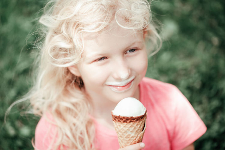 Girl eating licking ice cream from waffle cone. child eating sweet cold summer food outdoor