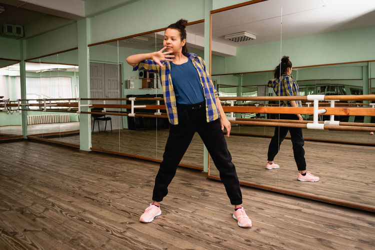 Pretty young woman showing dance move while engaged in contemporary dance alone in choreography hall