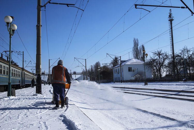 railway employee cleans the platform with a manual snowplow Employee Adult Architecture Building Exterior Built Structure Cable Cleans Clear Sky Cold Temperature Day Electricity  Electricity Pylon Fuel And Power Generation Full Length Mammal Manual Manual Men Nature One Person Outdoors People Platform Platforms Power Line  Railway Real People Sky Snow Snowplow Technology Transportation Winter
