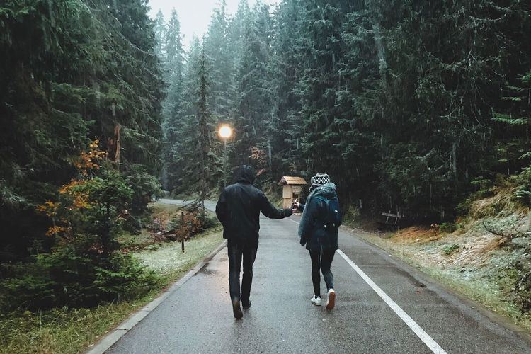 Rear View Of Couple Walking On Road In Forest During Rainfall
