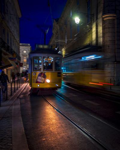 Car on illuminated street in city at night