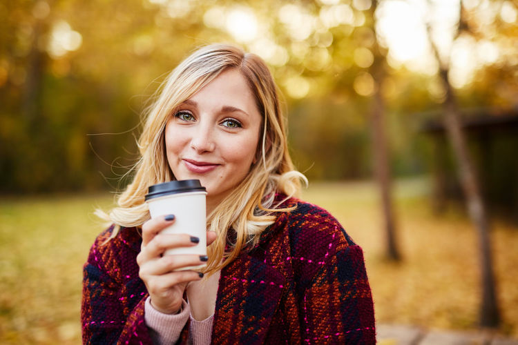 Beautiful Woman Blond Hair Close-up Day Focus On Foreground Front View Happiness Holding Leisure Activity Lifestyles Looking At Camera Nature One Person Outdoors Park - Man Made Space People Portrait Real People Smiling Technology Tree Wireless Technology Young Adult Young Women