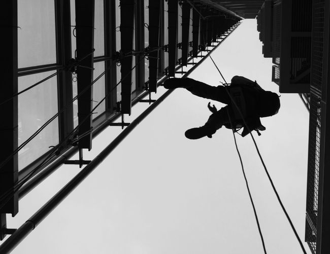 Low angle view of window washer amidst buildings