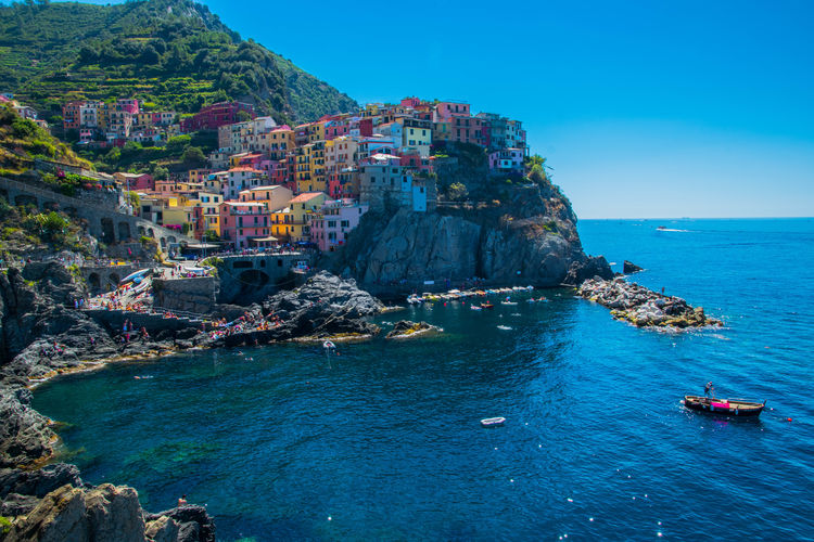 Buildings on cliff by sea at cinque terre