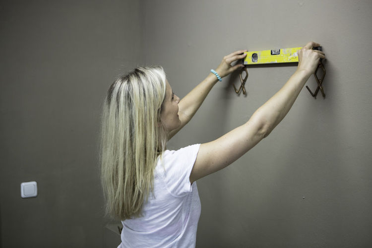 Side view of woman holding level with coat hooks on brown wall