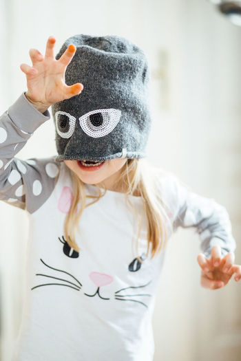 Having Fun Eyes Real People Girls Hair Portrait Child White Childhood Innocence Funny Faces Clothing Indoors  Front View Lifestyles Knitted Hat One Person Casual Clothing Waist Up Leisure Activity Focus On Foreground Obscured Face Missing Tooth Preschool School Children