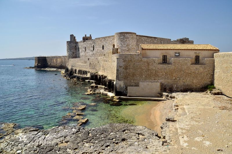 Maniace Castle in Syracuse Syracuse  Siracusa Sicily Sicilia Italy Italia Castello Maniace Beauty Natural Viaggio Travel View Mare Sea Street Photography City Art Archaeological Sites Arte Archaeology Archeological Site Explore Town Landscape Vista Rovine History Building Exterior No People Travel Destinations Built Structure Built Structure Built Structure Architecture Water The Past Ancient Beach Prison Old Ruin Day Castle Clear Sky Fort Nature Outdoors Sand Sky