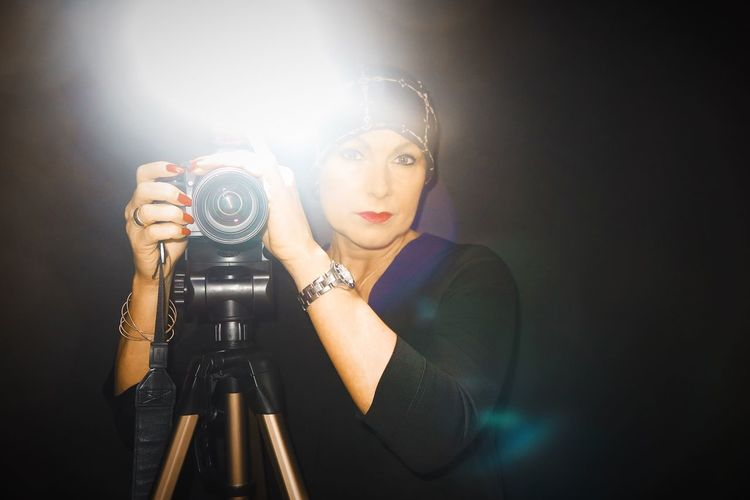 Portrait of woman photographing against black background