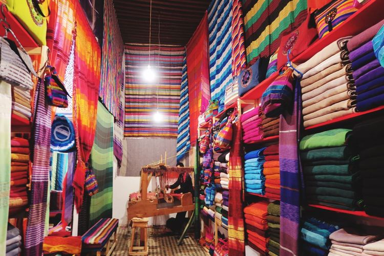 Worker working at workshop amidst multi colored fabrics