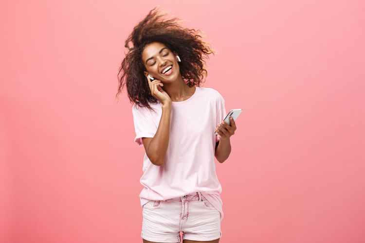 Beautiful young woman talking on phone while standing against pink background