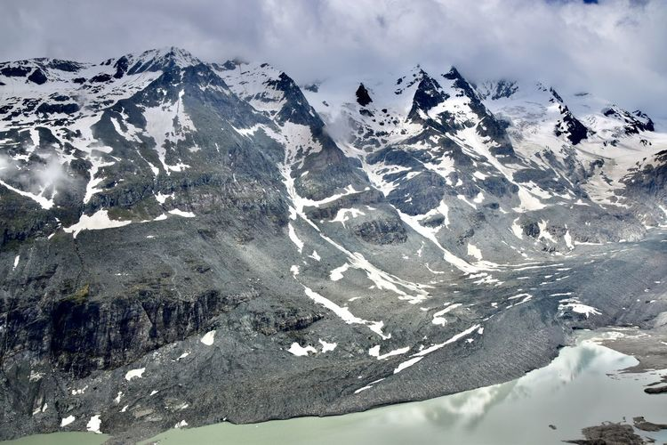 Aerial view of glacier lake and snowcapped mountains against sky