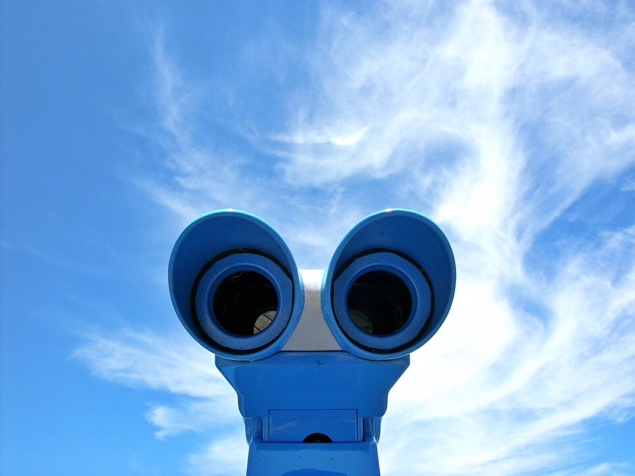 Close-up of binoculars against cloudy sky