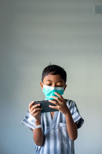 Portrait of boy holding mobile phone against wall