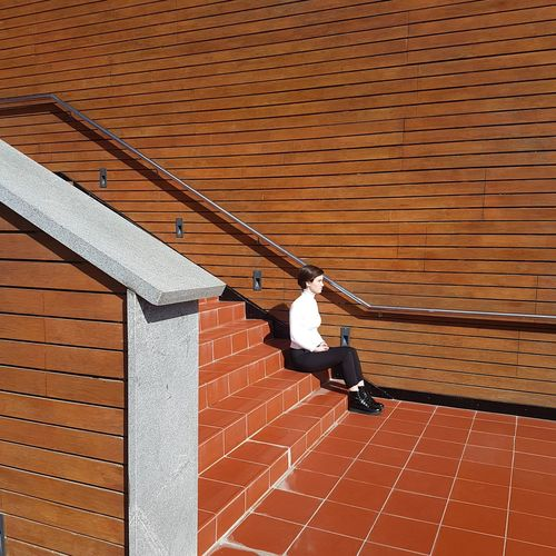 Side view of woman sitting on staircase