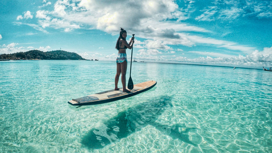 Woman standing in sea against sky-paddle boarding