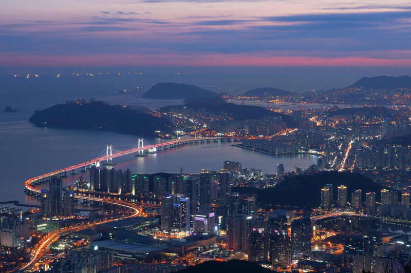 Aerial view of gwangandaegyo over sea by illuminated cityscape during sunset