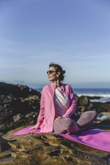 Mature woman exercising while sitting over mat on rock by sea against sky