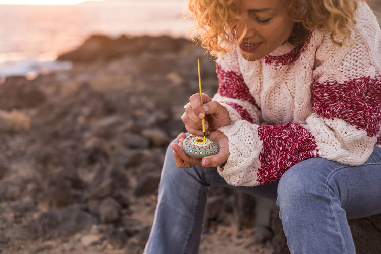 young woman curly hair sitting close the sea in relaxed moment vintage dressing Adult Beach Blond Hair Curly Hair Day Freshness Girls Holding Leisure Activity Mandala Nature One Girl Only One Person Outdoors Painting People Real People Relaxed Moments Sitting Smiling Stones Sunrise Sunset