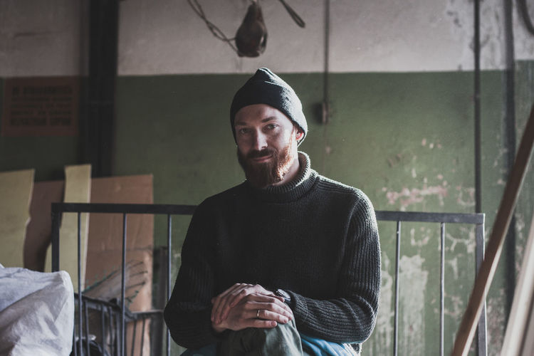 Portrait of smiling man wearing knit hat sitting indoors